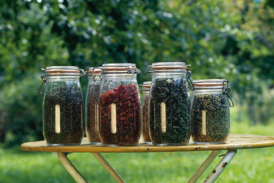 Kraeutertee in Glaesern Einmachgläser mit verschiedenen Teesorten auf einem Holztisch. © Österreich Werbung, Fotograf: Wiesenhofer